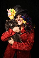 Caucasian woman in unique makeup and clothing holding black Pomeranian dog against black background