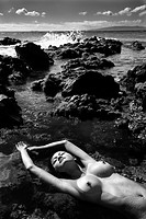 Woman lying on back in water on rocky beach