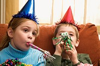 Caucasian children looking bored wearing party hats and blowing noisemakers (thumbnail)