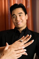 Prime adult Asian female admiring engagement ring with male in background