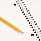 Sharp pencil placed on open spiral bound notebook