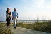 Caucasian mid_adult couple holding hands and walking down walkway at beach