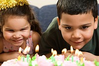 Hispanic girl and boy leaning in close looking at lit candles on birthday cake and smiling