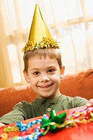 Caucasian boy wearing party hat holding gift and smiling at viewer.