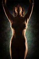 Nude Caucasian woman looking up with arms raised over head
