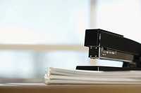 Black stapler on stack of paper with window in background (thumbnail)