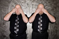 Caucasian bald mid adult identical twin men standing with hands covering eyes