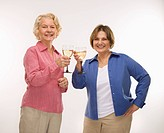 Caucasian senior woman and middle aged woman toasting wine glasses and smiling at viewer