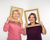 Mature woman and senior woman holding picture frames over faces