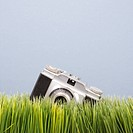 Studio shot of vintage camera in grass
