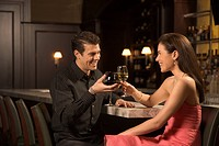 Mid adult Caucasian couple at bar toasting wine glasses and smiling
