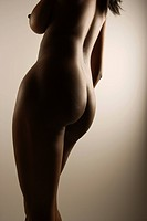 Nude African American mid adult female with back to viewer showing breast and hips