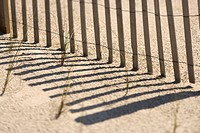Close_up of fence and shadows on beach Bald Head Island, North Carolina