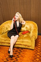 High angle view of a attractive Caucasian woman talking on red retro phone