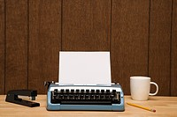 Vintage typewriter, coffee cup, pencil and stapler on desk