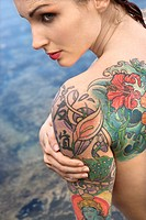 Back view of sexy nude tattooed Caucasian woman by tidal pool