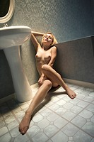 Attractive nude young adult Caucasian blond woman sitting on bathroom floor.