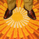 Close_up of Caucasian mid_adult male feet in vintage boots against sunburst rug