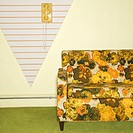 Retro floral printed sofa with yellow rotary phone hanging on wall