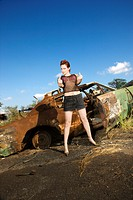 Sexy tattooed Caucasian woman standing giving middle finger in front of old rusted car in junkyard
