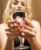 Attractive Caucasian woman holding a martini out to viewer