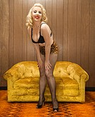Attractive Caucasian woman in lingerie posing in retro room