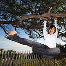 Young adult Asian female holding on to tree and kicking air and screaming