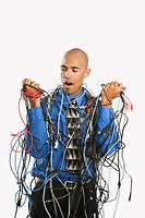 Confused businessman tangled in cables