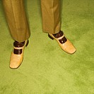 Close_up of Caucasian mid_adult male feet in vintage shoes against green rug