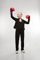 Caucasian senior woman wearing boxing gloves raised in the air