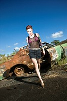 Sexy tattooed Caucasian woman walking towards viewer seductively in junkyard