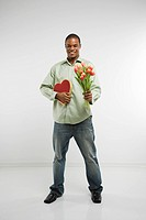 Studio shot of African_American man holding valentine heart and bouquet of tulips smiling and looking at viewer
