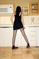Back view of pretty Caucasian young woman standing in kitchen