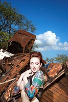 Partially nude attractive tattooed Caucasian woman standing in junkyard