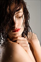 Portrait of bare attractive Caucasian redhead young woman with wet hair and skin.