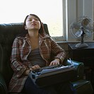 Pretty young Asian woman sitting in chair with typewriter on lap