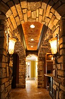 View of foyer through stone archway in affluent home
