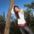 Young adult Asian female with one hand on tree and other hand giving the viewer the middle finger