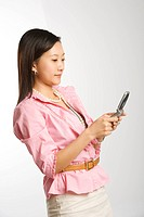 Portrait of Asian Chinese mid_adult female text messaging on cell phone