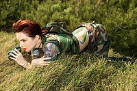 Attractive tattooed Caucasianwoman in camouflage lying on grass looking through binoculars
