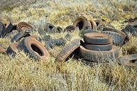 Old dirty abandoned tires in field