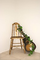 Still life of guitar with garland leaning against a chair