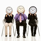 Multi_ethnic business people sitting holding clocks over faces