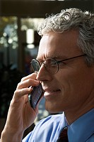 Close up profile of prime adult Caucasian man in suit talking on cellphone