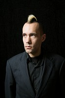 Portrait of Caucasian man in suit with mohawk against black background