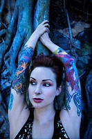 Blue_toned portrait of tattooed Caucasian woman with Banyan tree