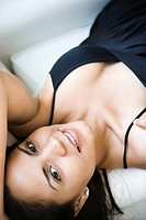 Smiling Hispanic woman lying down and looking at viewer