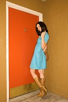 Caucasian young adult woman in retro clothing standing at doorway looking at viewer
