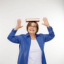 Caucasian middle aged woman balancing book on head