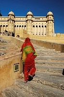 Woman in orange sari walking up to Amber Fort  Jaipur  India